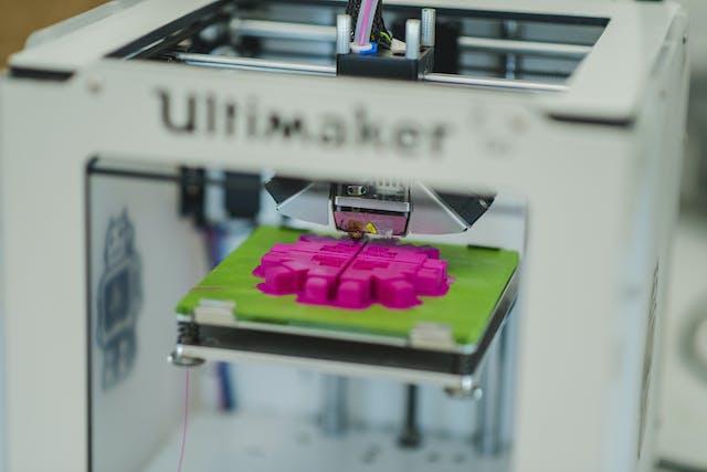 An Ultimaker 3D printer prints a neon pink shape on a green platform