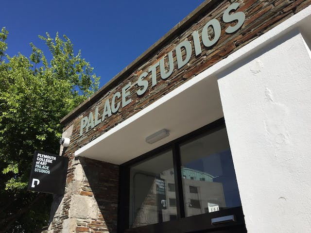 """alt=""""A vibrant blue sky frames our Palace Studios campus building, with original brickwork and white walls. A tree stands high next to the entrance."""""""