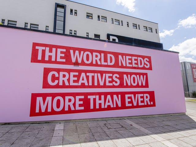 The World Needs Creatives mural on front of Plymouth College of Art building