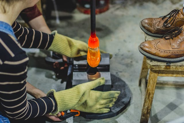 Glowing from the furnace, a hot orange blob of molten glass is carefully placed for shaping, the students wear protective gloves.