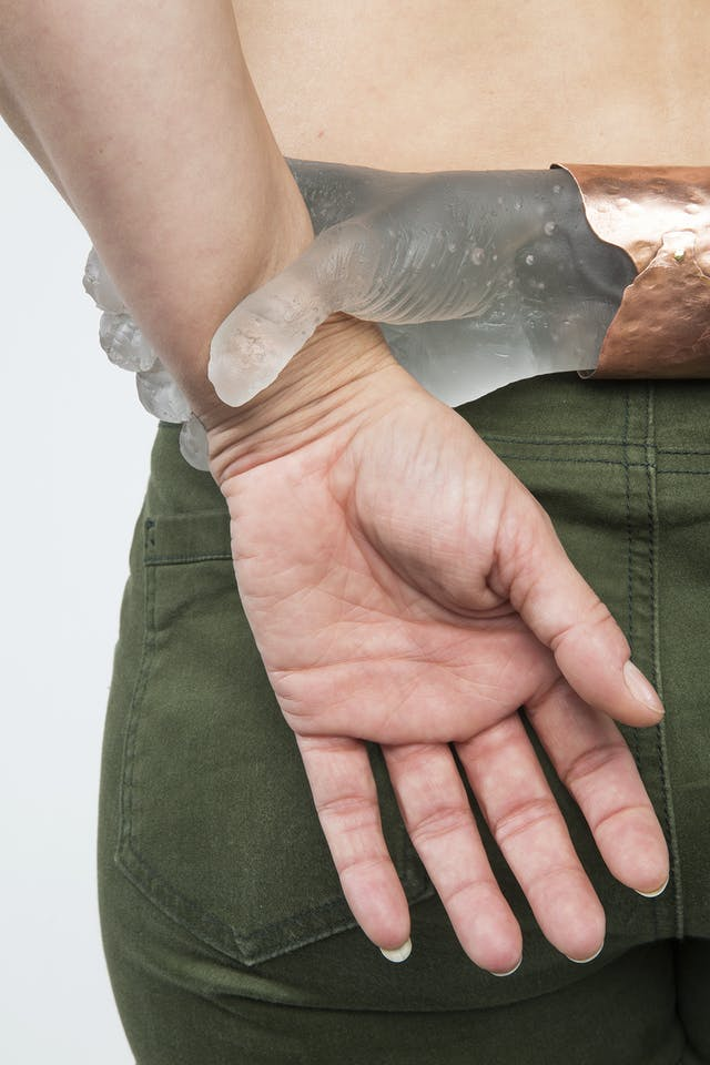 A copper edged glass sculpture of a hand firmly grips the wrist of a real human hand, placed behind the subject's back, leaf green trousers are visible beneath.