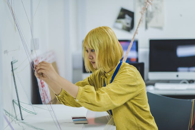 A girl in a yellow top sits at a desk working on an art sculpture built from multicoloured strings.