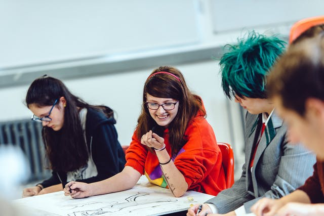 A young art student in a red jumper shares a joke with friends whilst drawing on a big sheet of paper with charcoal