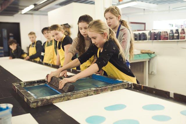 Young Art students wearing yellow aprons watch as a girl screenprints onto a long sheet of paper