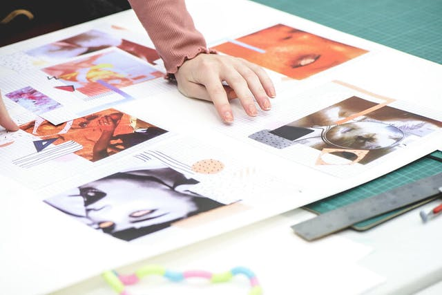 A young hand delicately rests on a moodboard featuring printed photographs with illustrated elements drawn on top of them placed on a green cutting mat