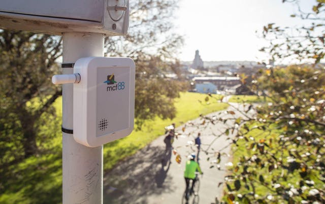 Image of an environmental park sensor high up on a pole overlooking someone riding a bicycle wearing high vis, a couple other people walking and trees and a park in the background