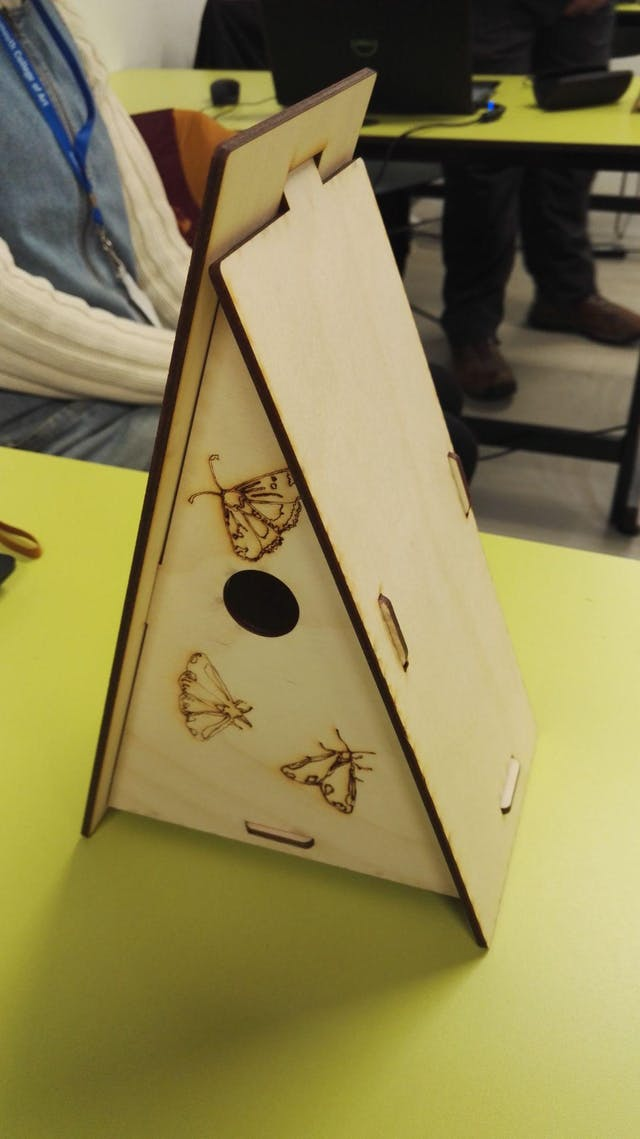 Image shows a lazer cut bird house in a triangle A frame type design made out of wood