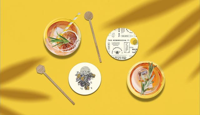Image shows an overhead view of cocktails featuring stirrers and coasters with the Kombeecha Co. branding which features an illustrated bee and typography