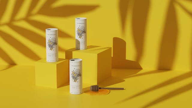 Image shows three kombucha drinks on mustard yellow boxes against a mustard yellow background with shadows of leaves, as well as a honey stirrer in the foreground. The drinks show the illustrated bee branding.