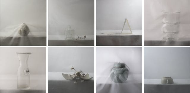 Image shows a series of objects on a surface, shrouded in sheer fabric and with muted tones and lighting