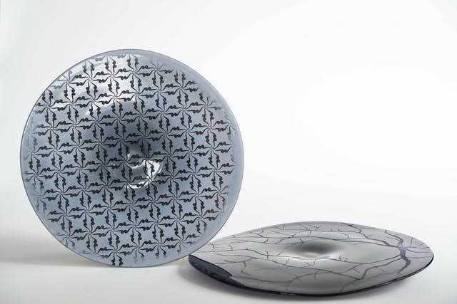 Image shows two glass discs in shades of bluey grey, one flat on the surface, another on its edge, with etchings and patterns