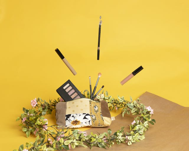 Image shows make up products flying out of a recycled fabric make up bag, with floral elements around and a strong mustard yellow background