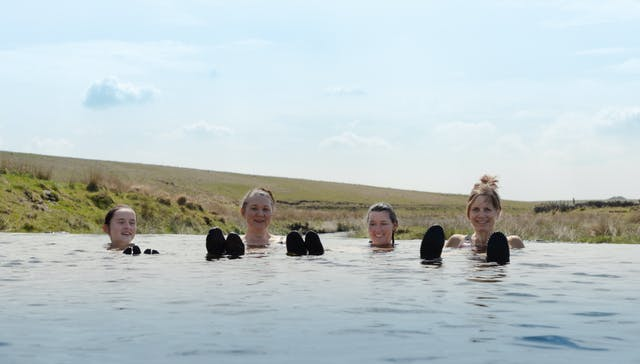 Image shows four women floating in natural water with smiles on their faces and Dartmoor in the background. You can see some of their swimming booties in the foreground, popping through the water.