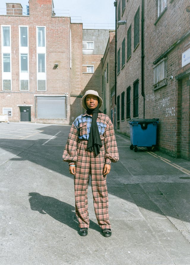 Image shows a woman stood in the middle of a street, with brick buildings around her. She is dressed in a checkered suit and bucket hat and looking directly at the camera.