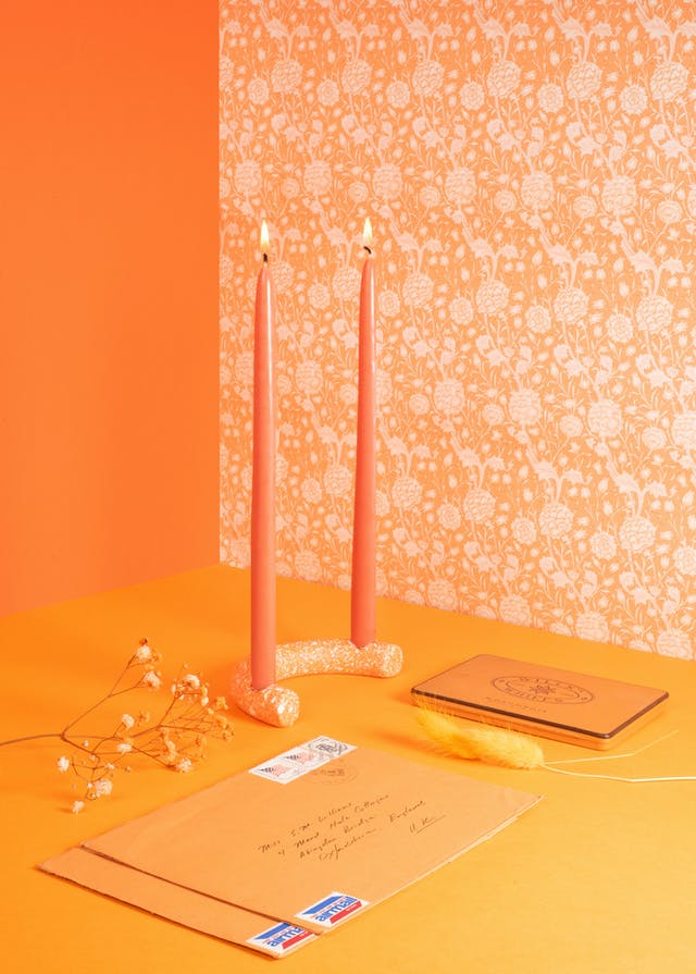 Image shows a room coloured with similar shades of orange with orange objects in the foreground including letters, candles and a feather