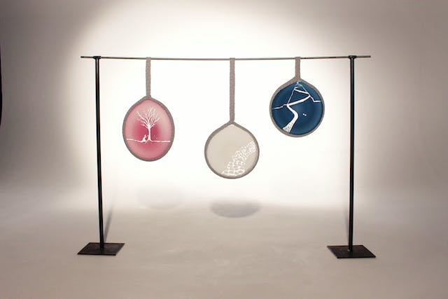 Image shows three glass discs in different colour and with natural etchings and detail hanging from a black metal frame