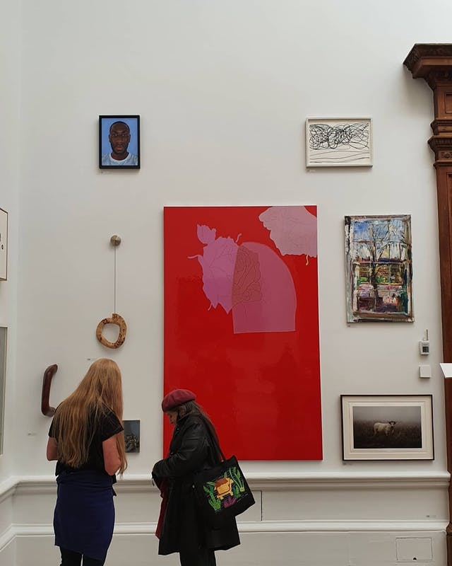 Xanthe's painting in place in the Royal Academy of Arts, two people stand to the left hand corner of the photo looking at the paintings, one of which is large and red with pink, surrounded by smaller paintings and framed pictures