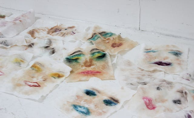 Scattered rectangular pieces of fabric with smudged images of faces on a white background work by Darcy for Testspace at Karst June 2021 Photos by Eloise Dodsworth