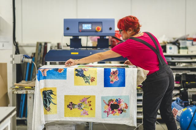 Lecturer Becky Dodman Wainwright uses the industrial heat press in textile studio to print cat and flowers design on fabric