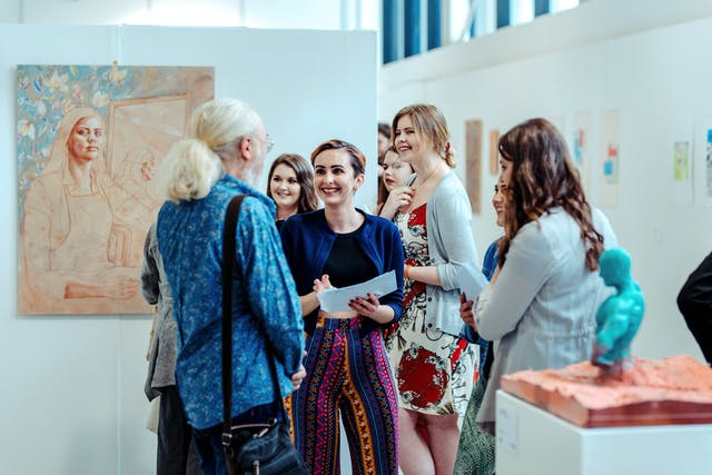 Four women smile and speak to a man in a gallery space with paintings hung on the walls