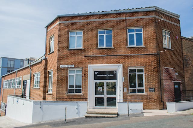 """alt=""""Our red brick Postgraduate Centre curves around the corner of the street with the blue sky and sun reflecting off the many windows."""""""