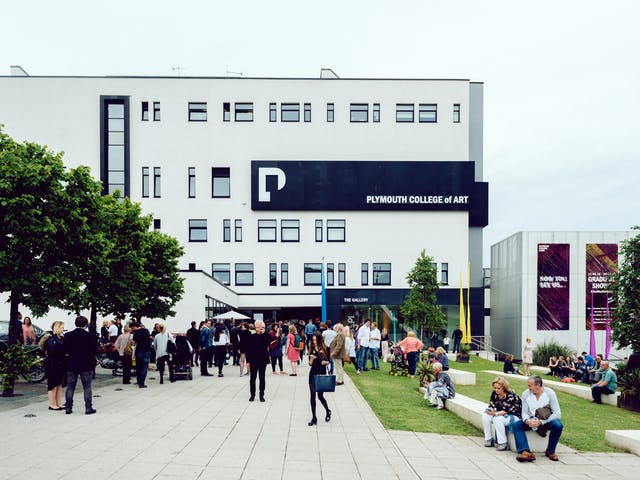 Brightly coloured banners and lush green trees frame the entrance to our undergraduate campus building as people enjoy the space
