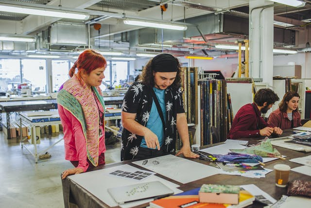 Lecturer Becky Dodman stands next to a textiles student and discuss his work laid out on the print table in front of them, a mix of bright colours and fabrics in our bright and open print studio
