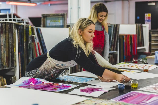 A student leans across a print table covered in large sheets of paper coloured with inks ready for heat transfer printing to fabric.