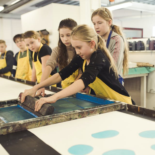 Group of young people in aprons having a go at screenprinting in Plymouth College of Art's textile workshop