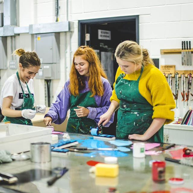 Gathered around a printing station, three female students laugh in paint-splatted aprons whilst hand-rolling ink.