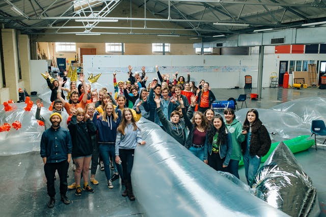 A large class of school-age students pose for a photo in an industrial-looking warehouse with inflatable installations.