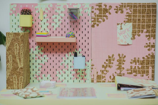 A pink desk with pastel coloured stationary