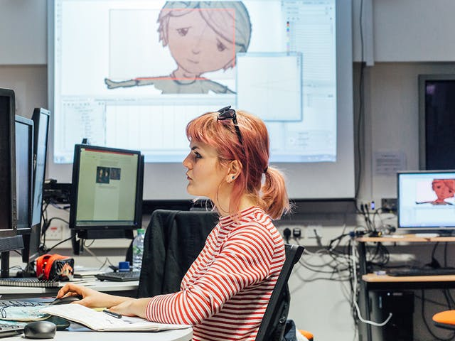 A girl in a striped top sits at a computer with a character projected onto a screen behind her web