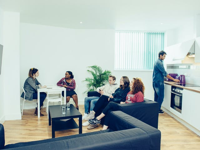 Five students sit on a black sofa, at a white table, whilst one puts the kettle on in the kitchen. The space is bright and clean and is one of Clever Student Lets' shared halls.
