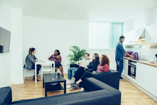 """alt=""""Five students sit on a black sofa, at a white table, whilst one puts the kettle on in the kitchen. The space is bright and clean and is one of Clever Student Lets' shared halls."""""""