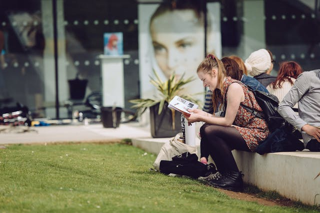 """A female student sits in a grassy area with fellow students on a concrete bench outside The Gallery window smiling whilst reading"""