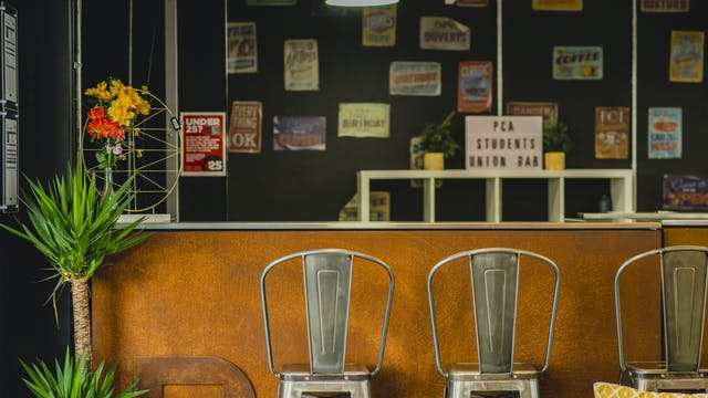 """alt=""""A warm rusted copper bar is framed by plants and high metal stools in our Students' Union bar. Behind the bar on the wall are vintage posters."""