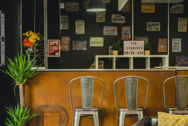 A warm rusted copper bar is framed by plants and high metal stools in our Students' Union bar. Behind the bar on the wall are vintage posters.