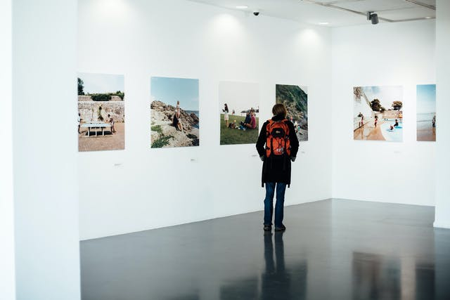 A woman stands in a white gallery space looking at large printed photographs of people at the seaside.