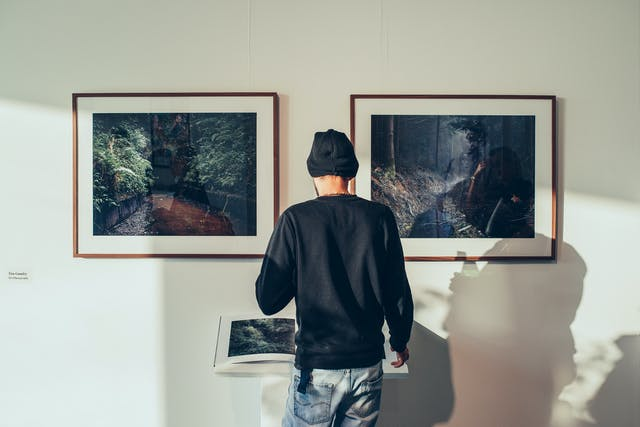 A man stands in a white gallery space looking at two framed photographs showing landscapes of forests.