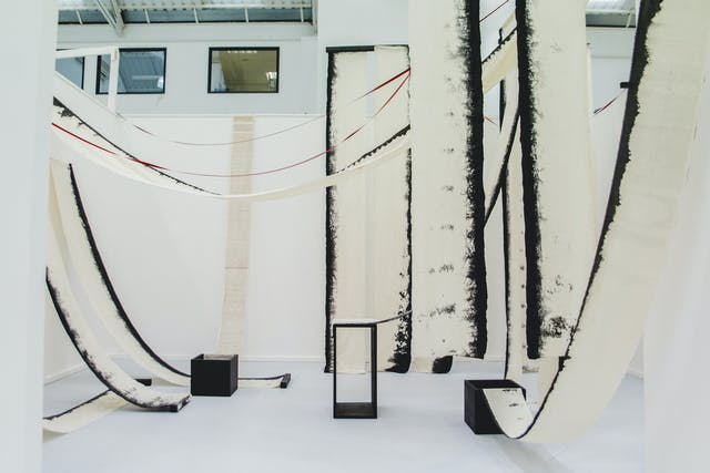 In a white exhibition space, long pieces of off-white fabric hang from the ceiling with the ends tucked into black boxes. The material has black edges with small text printed on it.
