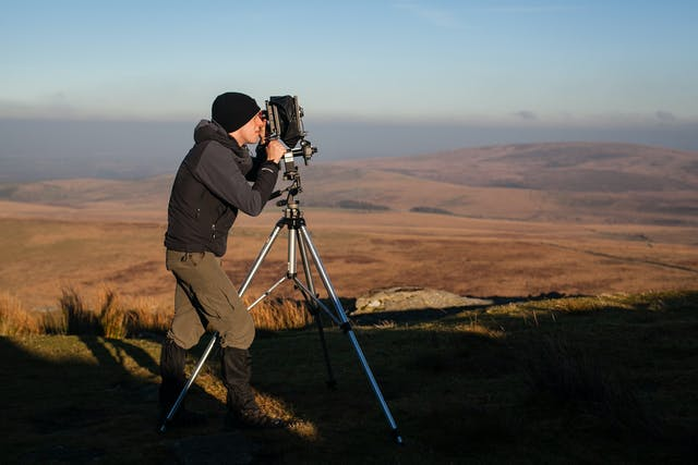 Graduate Nicholas White stands at the top of a tor in Dartmoor looking through the lens of a large 5x4 film camera as the rich golden light of the morning sun brings the moorland to life around him.