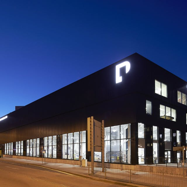 Charles Cross Building at night. Floor to ceiling windows are lit from the inside, allowing passers-by a peer into the Crafts Studios where glassblowing, pottery, jewellery-making and more take place.