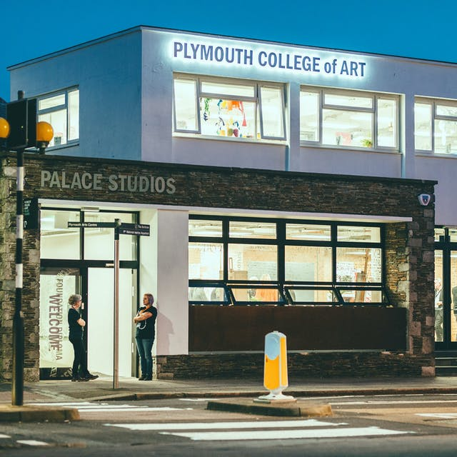 "A pelican crossing of black and white stripes leads up to the Pre-Degree Campus Main Entrance. Two staff members lean in the main entrance, dimly lit by the building signage which states ""Plymouth College of Art"", words glowing against a dark sky."