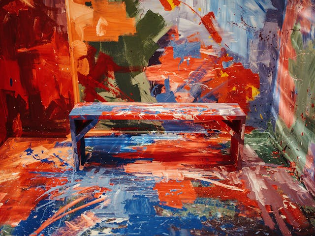 A bench sits alone in a room, camouflaged by paint strokes and splatter in a rainbow of colour. The walls and bench merging into one.