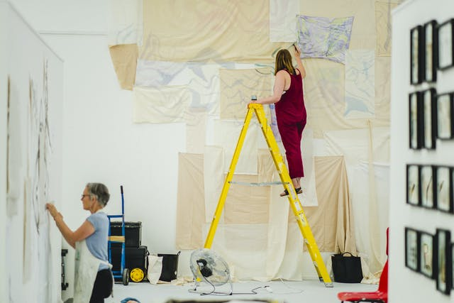 Two female students take over the postgraduate studios, one up a bright yellow ladder layering neutral shades of cloth and paper, the other kneeling on the floor to carefully pin her work.