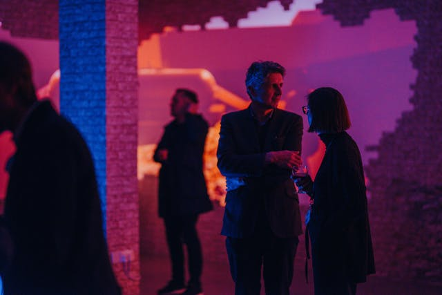 Silhouettes of four staff and student gallery visitors roam an ambient room of multicolour light and video projections. A brick column cuts through the middle.