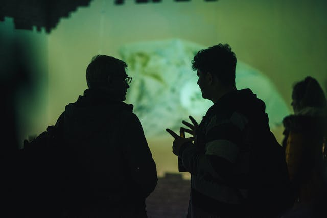Two male students speak in silhouette against a background of experimental green lighting at the college's on-site gallery.