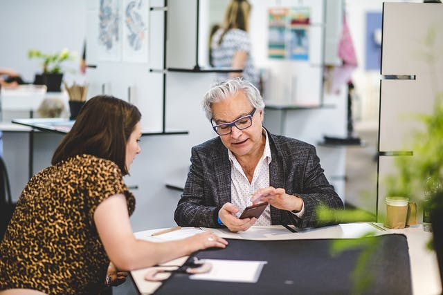 London Design Fair 2017 A woman shows her portfolio to an older man with glasses sitting at a desk at London Design Fair