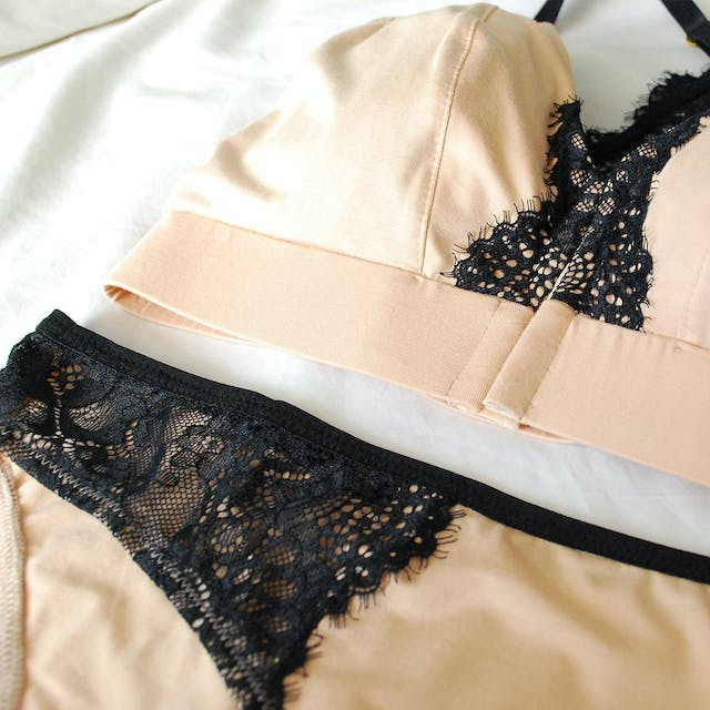 Cream and black lace lingerie laid on a white sheet
